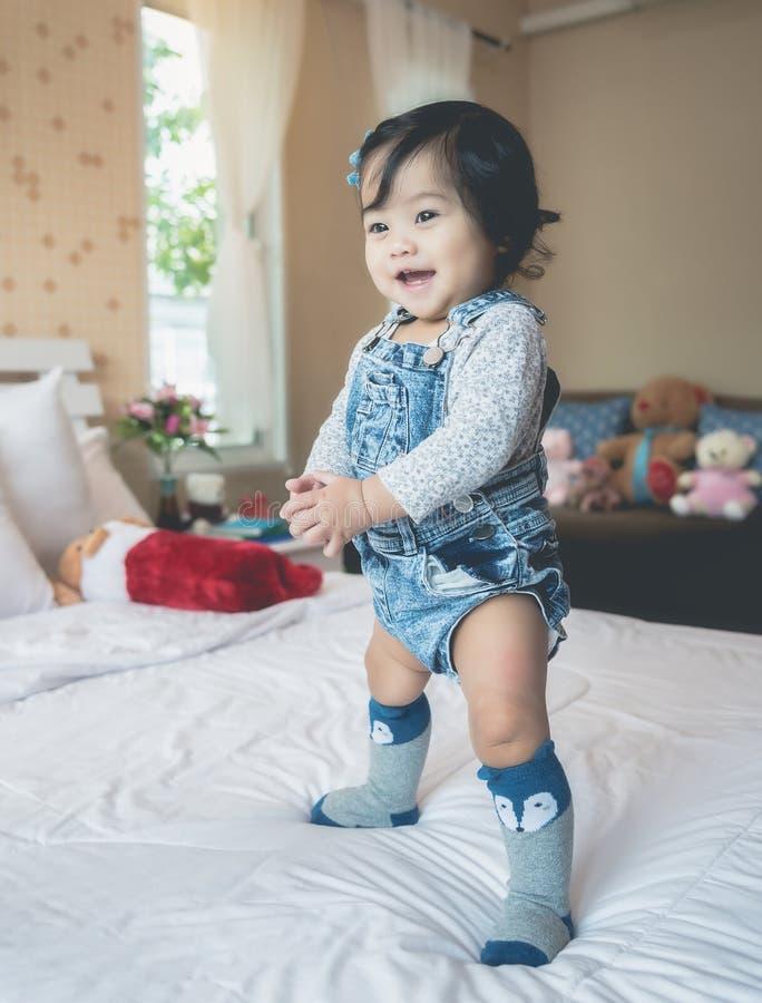Una neonata asiatica sta giocando nel suo letto con un'espressione felice fotografie stock