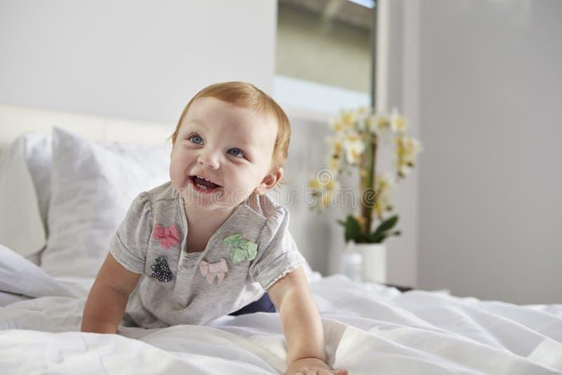 Una neonata felice che striscia su un letto, spazio della copia sulla destra fotografie stock