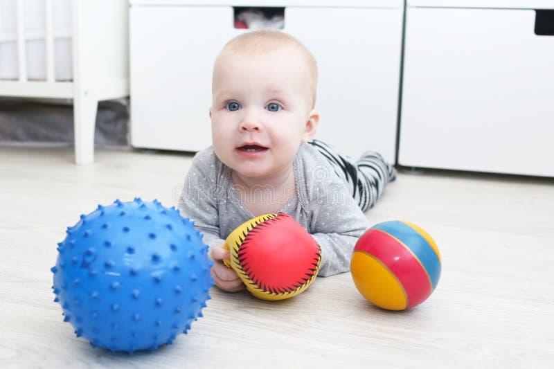 Una neonata piacevole da 6 mesi gioca le palle immagine stock libera da diritti