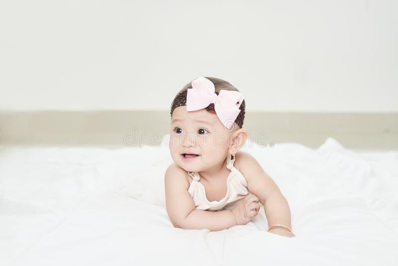 Una neonata sta strisciando lungo il pavimento con uno sguardo inquisitore fotografia stock libera da diritti