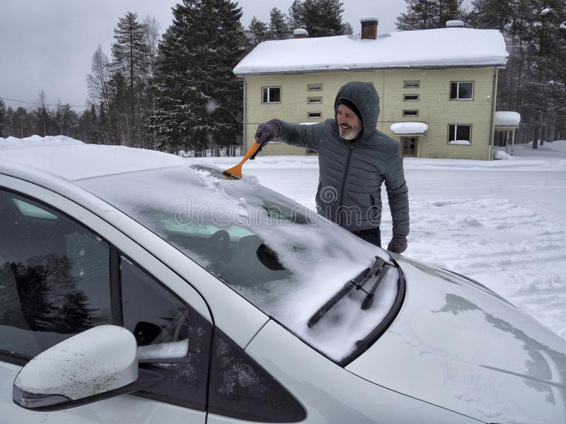 Una neve di pulizia dell'uomo dal parabrezza dell'automobile con la spazzola Rimuovendo neve dall'automobile fotografia stock libera da diritti
