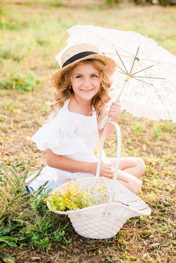 Una niña agradable con la luz se encrespa en un sombrero de paja, un vestido blanco y un paraguas del cordón con una cesta de flo imágenes de archivo libres de regalías