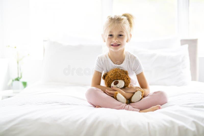 Una niña alegre en la cama que se divierte fotos de archivo libres de regalías