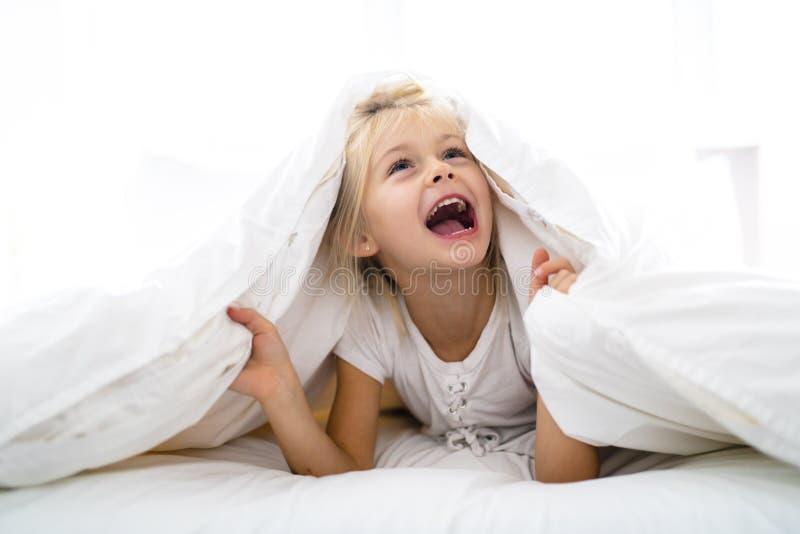 Una niña alegre en la cama que se divierte imagenes de archivo