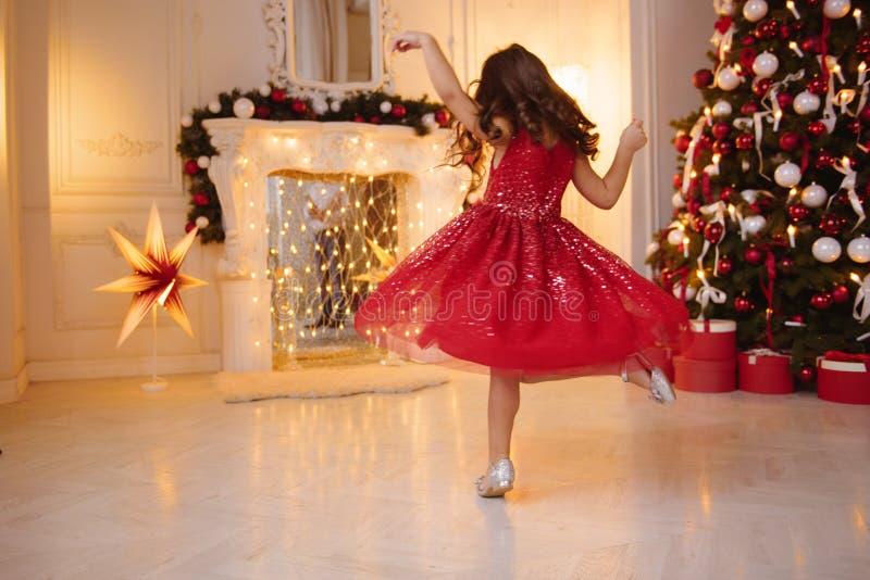 Una niña bonita con el pelo rubio que lleva el vestido rojo, brillante de la Navidad imagenes de archivo