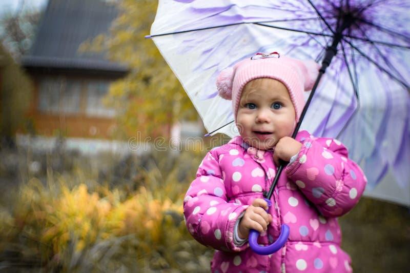 Una niña camina con un paraguas en la lluvia en el país imagenes de archivo
