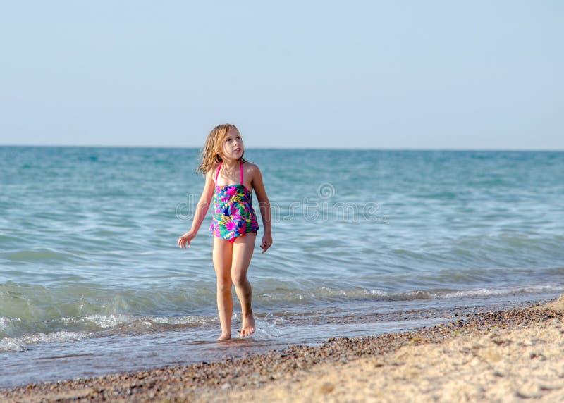 Una niña camina a lo largo de la playa que mira para arriba fotos de archivo libres de regalías