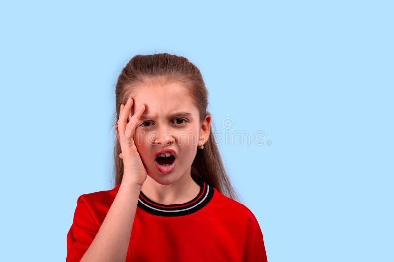Una niña clama contra del ultraje o del descontento que lleva a cabo su mano a su cabeza fotografía de archivo libre de regalías