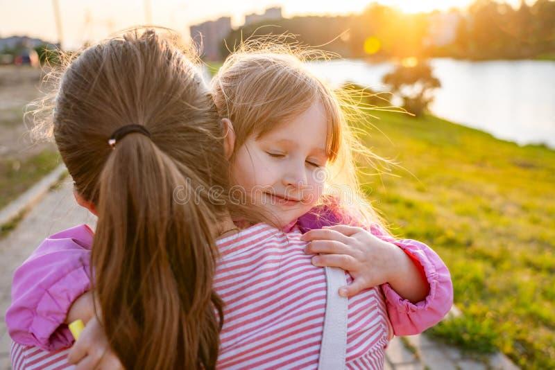 Una niña con amor abraza a su madre muy suavemente fotografía de archivo libre de regalías