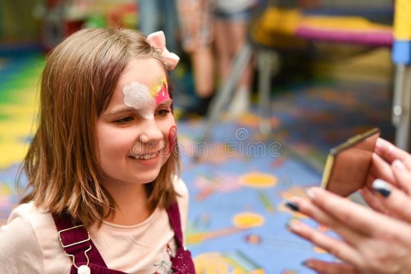 Una niña con una cara pintada mira se en el espejo en la fiesta fotos de archivo