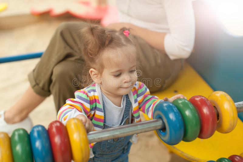 Una niña con dos colas en una blusa rayada juega un día soleado del verano en el patio fotos de archivo