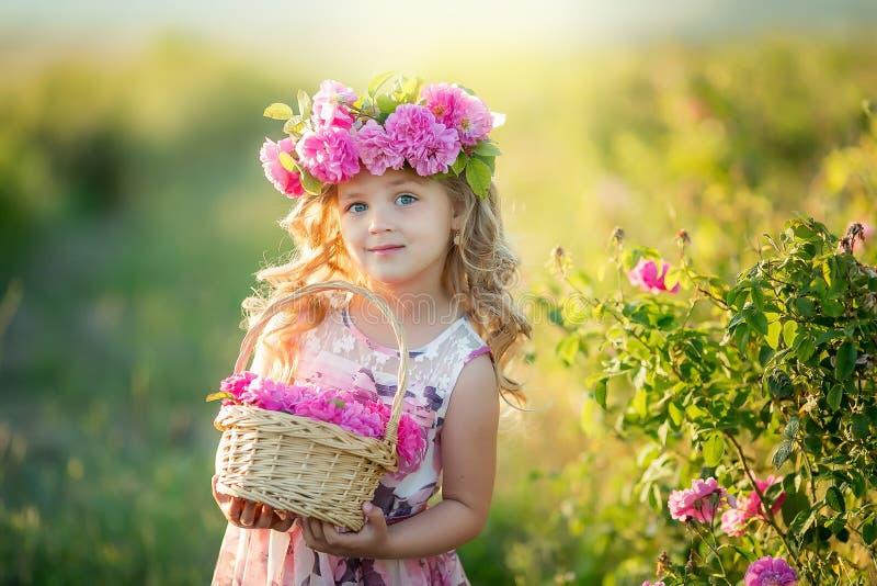 Una niña con el pelo rubio largo hermoso, vestido en un vestido ligero y una guirnalda de flores reales en su cabeza, en fotos de archivo libres de regalías