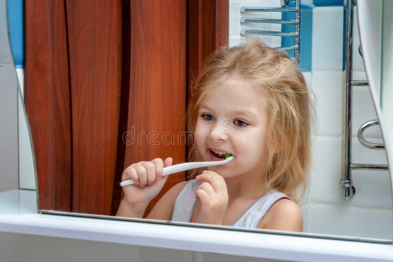 Una niña con el pelo rubio que cepilla sus dientes El niño sonríe en su reflexión en el espejo imagenes de archivo