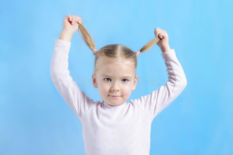 Una niña con el pelo rubio tira de sus colas en diversas direcciones El bebé lindo salpica y divertirse Foto brillante fotos de archivo libres de regalías
