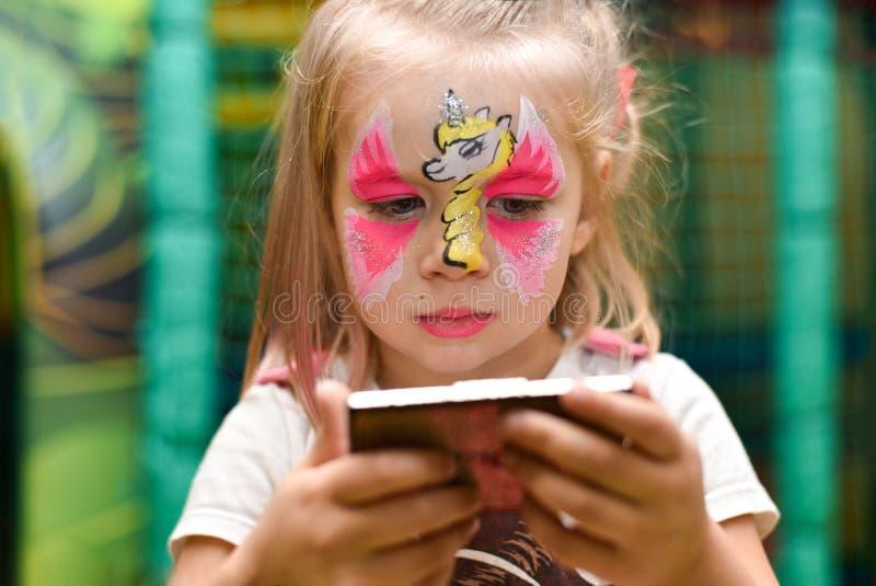 Una niña con un modelo de un unicornio en sus miradas de la cara en el espejo imágenes de archivo libres de regalías