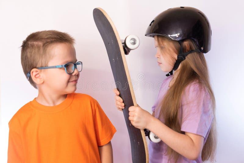 Una niña con un monopatín a disposición, resplandores en el niño pequeño en un fondo ligero imagen de archivo