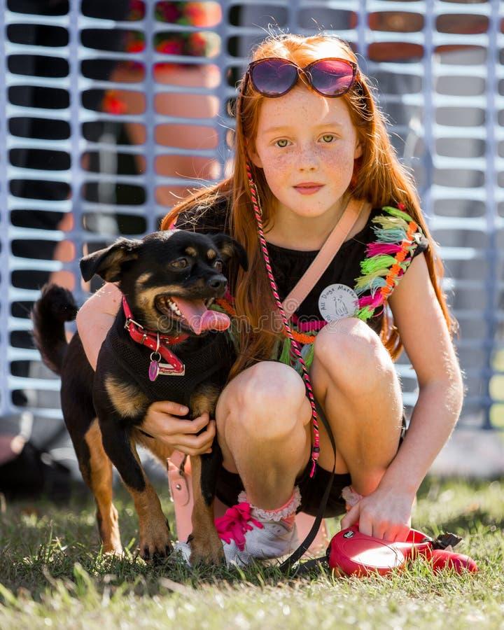 Una niña con un perro en el parque en una exposición canina imagenes de archivo