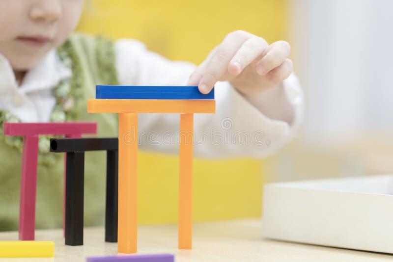 Una niña construye una casa del diseñador imagenes de archivo