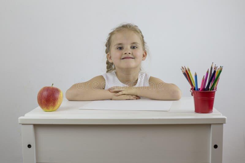 Una niña contenta se está sentando en su escritorio con lápices y una manzana madura imagen de archivo