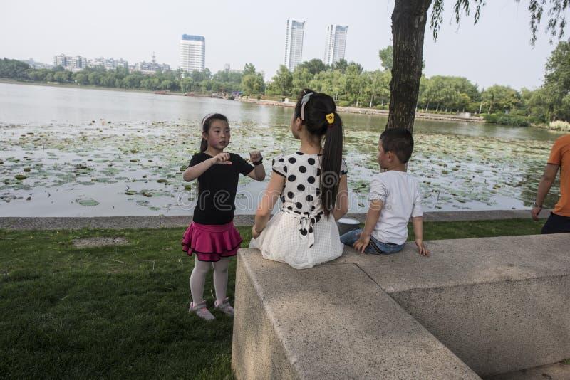 Una niña cuenta historias a dos niños en el lago Xuanwu fotos de archivo libres de regalías