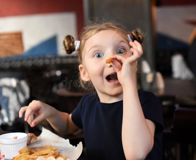 Una niña de risa que cena y que paga con la comida fotografía de archivo libre de regalías
