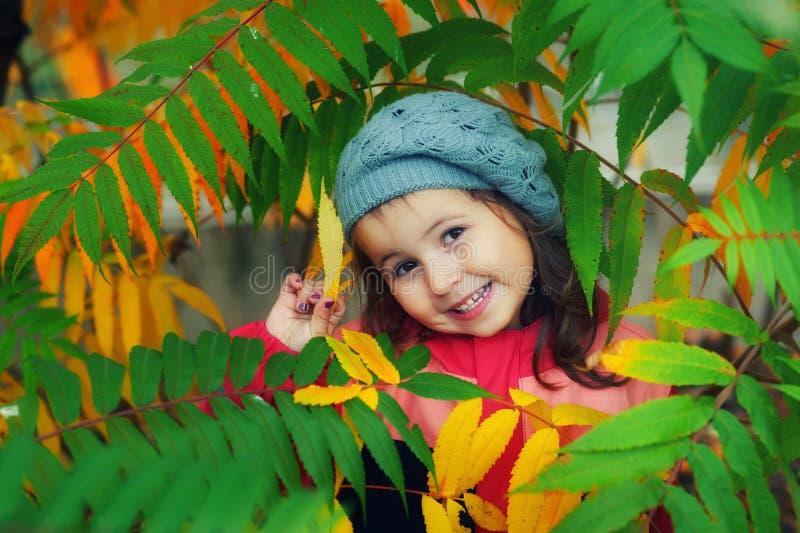 Una niña en una boina hecha punto para un paseo en un día del otoño imagenes de archivo