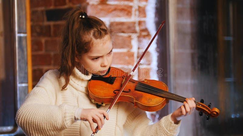 Una niña en el suéter blanco que toca el violín imagen de archivo libre de regalías