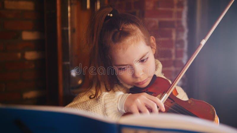 Una niña en el suéter blanco que toca el violín por las notas fotos de archivo