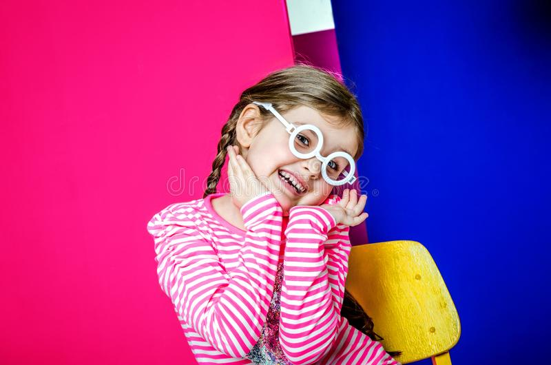 Una niña en los vidrios redondos blancos en un fondo coloreado brillante imágenes de archivo libres de regalías