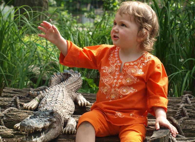 Una niña en ropa anaranjada brillante se está sentando al lado de un cocodrilo relleno en un fondo de la hierba verde imágenes de archivo libres de regalías