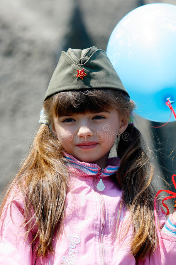 Una niña en un casquillo de guarnición militar en la celebración de Victory Day en la colina de Mamaev en Stalingrad imagenes de archivo
