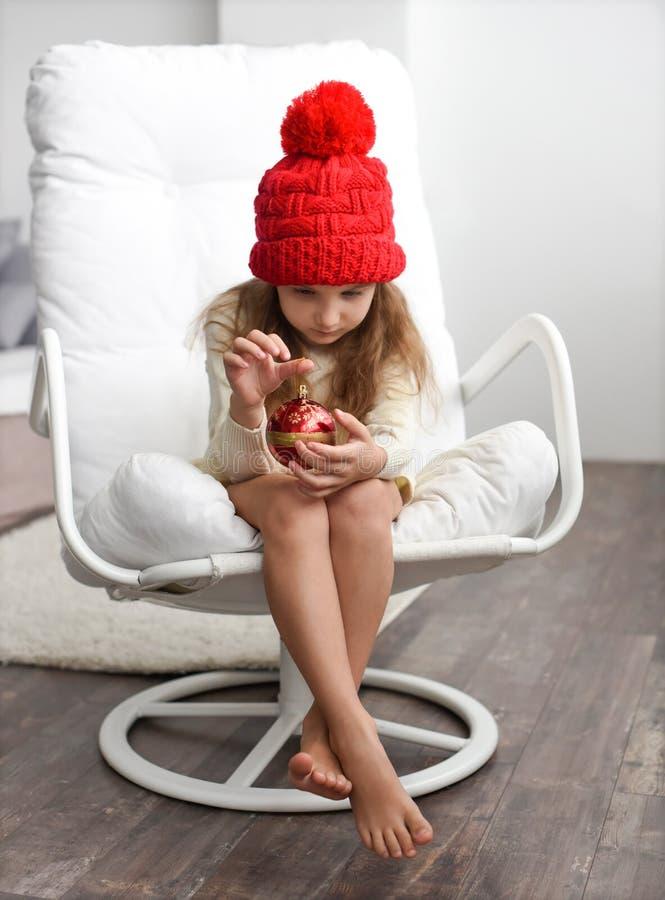 Una niña en un casquillo rojo hecho punto que sostiene decoraciones de la Navidad fotos de archivo libres de regalías