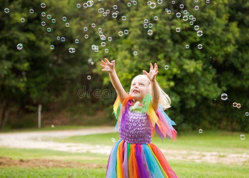Una niña en un traje brillante que persigue burbujas foto de archivo