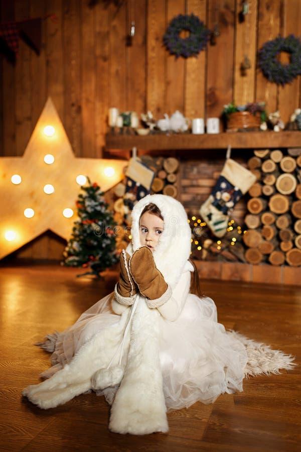 Una niña en un traje caliente blanco y guantes del oso se está sentando cerca de la chimenea En una casa en el árbol Concepto del imagenes de archivo