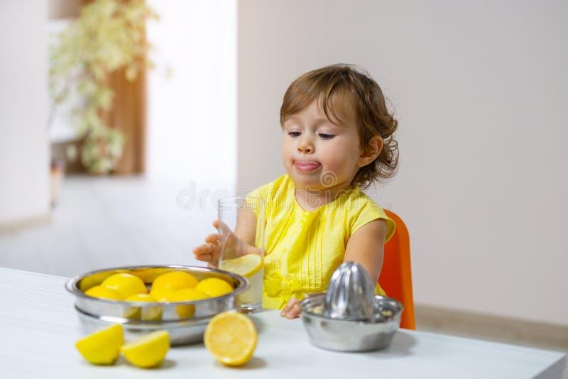Una niña en un vestido amarillo prueba la limonada cocinada fotos de archivo