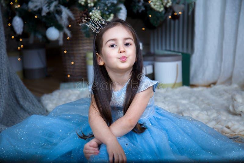 Una niña en un vestido azul hermoso en el árbol de navidad imagenes de archivo