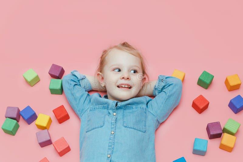 Una niña encantadora en ropa del dril de algodón está mintiendo en un fondo rosado entre los cubos coloreados de madera foto de archivo