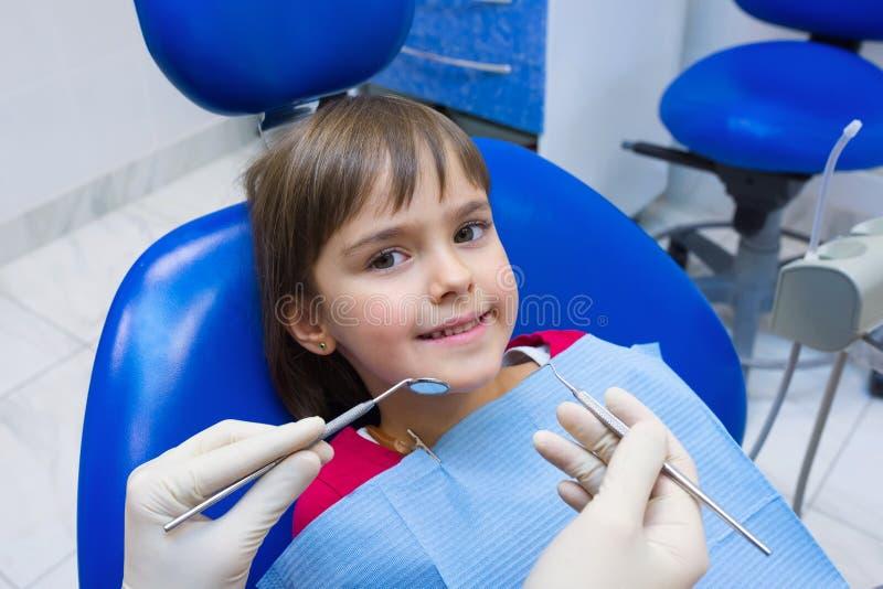 Una niña encantadora sentada en una silla dental en el hospital Las manos de un dentista infantil Una niña pequeña sentada en el  foto de archivo libre de regalías