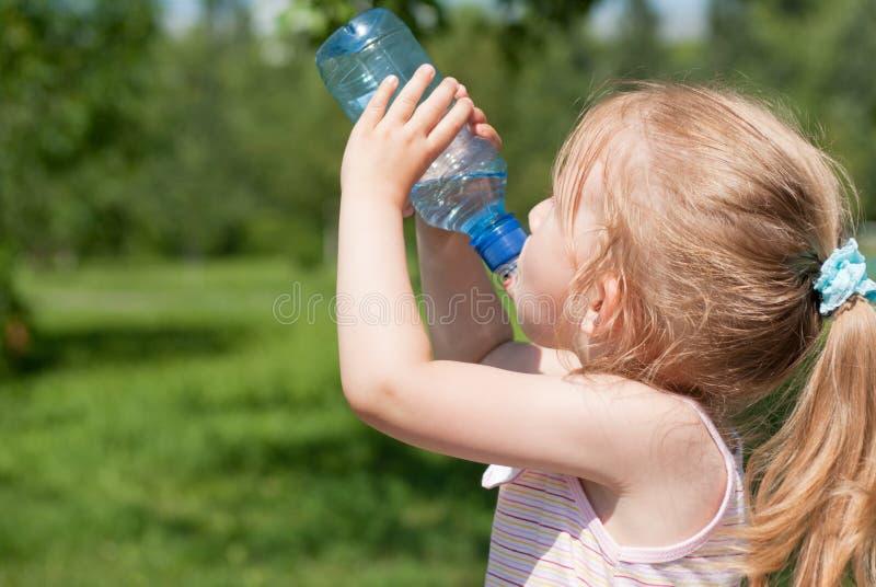 Una niña está bebiendo el agua potable imagen de archivo