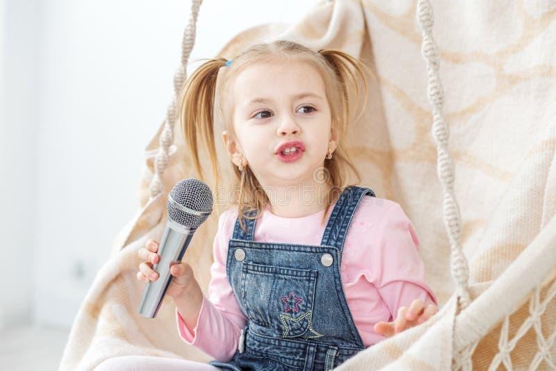 Una niña está cantando Karaoke en el micrófono El concep foto de archivo libre de regalías