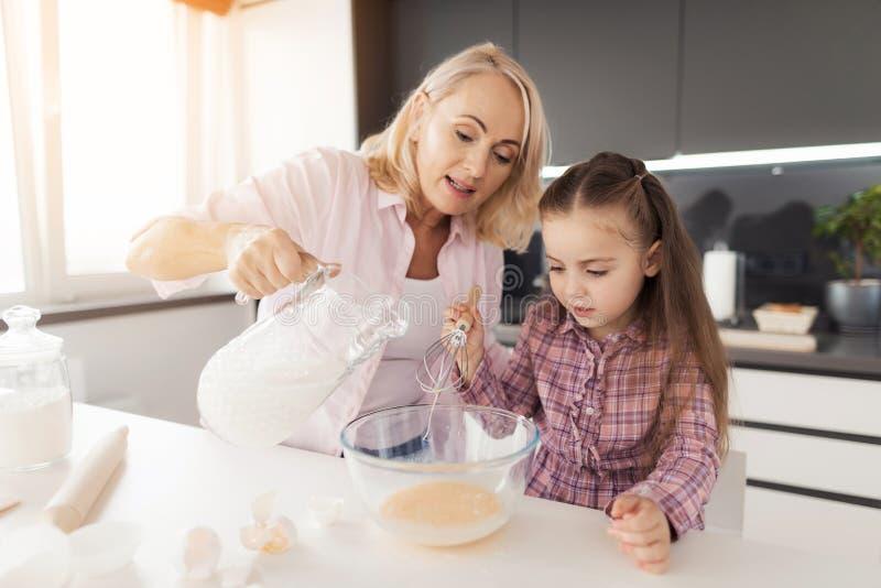 Una niña está cocinando una galleta hecha en casa La muchacha ha batido los huevos, la abuela vierte la leche en huevos imagenes de archivo
