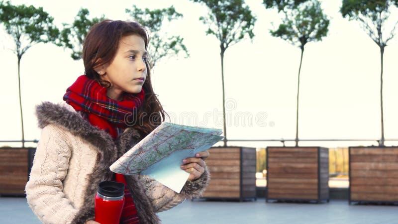 Una niña está estudiando un mapa y está mirando fijamente soñador en la distancia fotos de archivo libres de regalías