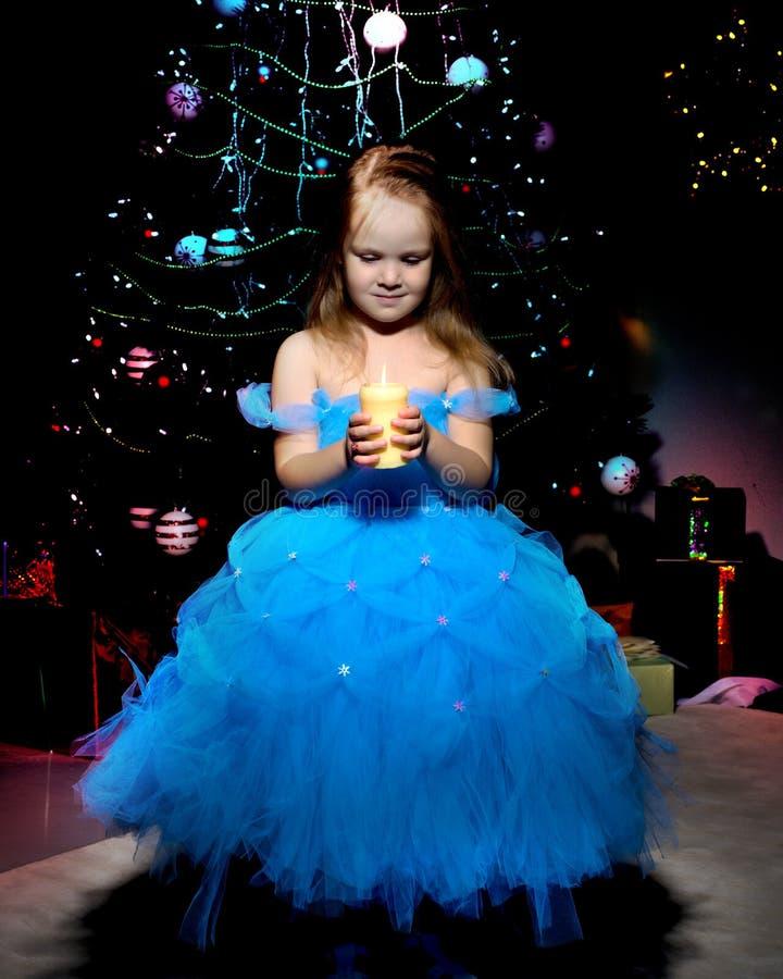 Una niña está llevando a cabo una vela fotos de archivo libres de regalías