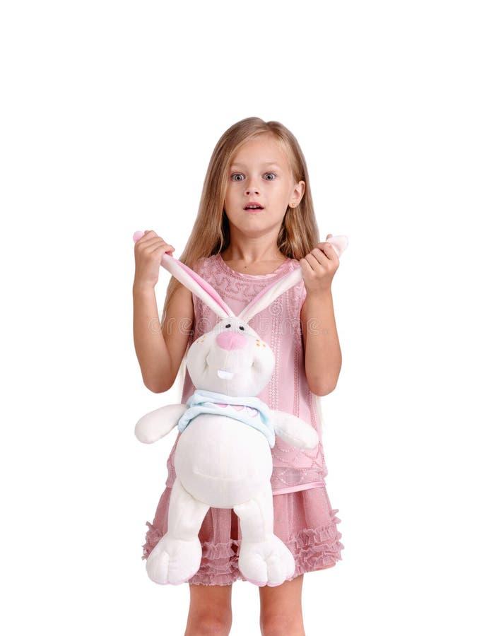 Una niña expresiva que sostiene una liebre suave juega, aislado en un fondo blanco Concepto de los niños, el jugar y del resto imagen de archivo