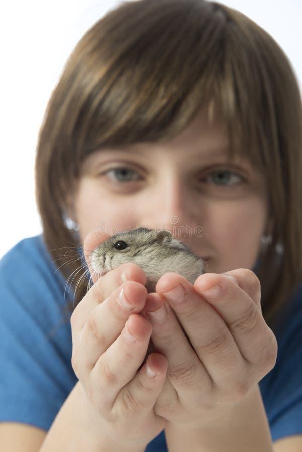 Una niña feliz con un hámster lindo imagen de archivo