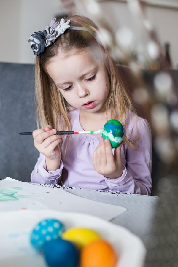 Una niña feliz que colorea los huevos de Pascua fotos de archivo