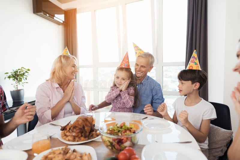 Una niña feliz se está sentando en una tabla festiva La familia celebra su cumpleaños imagenes de archivo