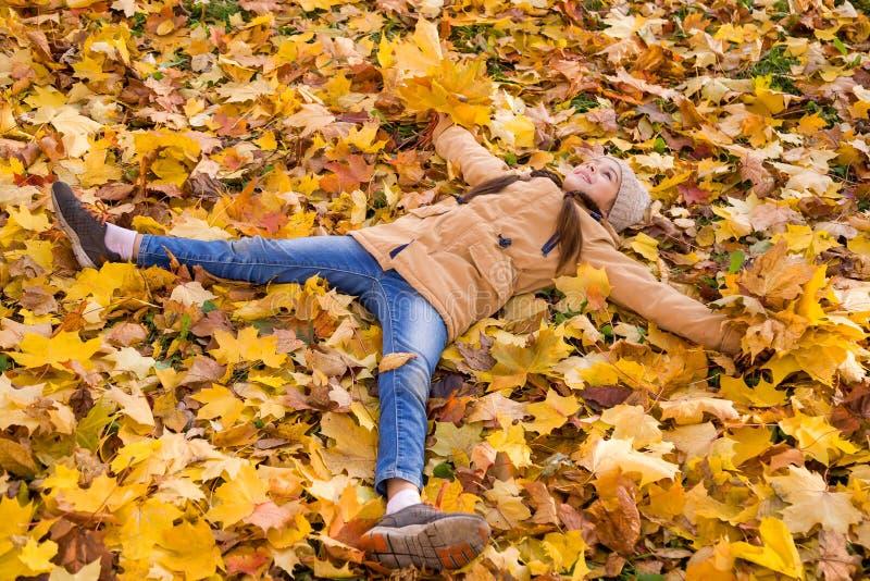 Una niña feliz tendida sobre los caídos deja los brazos extendidos y sostiene en sus manos los ramos de hojas de arce amarillas fotos de archivo libres de regalías