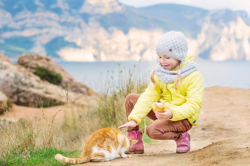 Una niña frota ligeramente y alimenta un gato rojo sin hogar foto de archivo libre de regalías