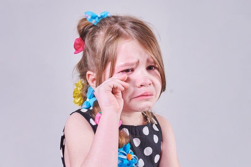 Una niña hermosa, con una expresión triste, llora y la limpia los rasgones con sus manos fotos de archivo